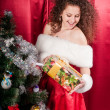 Girl with gifts near a Christmas tree — Стоковое фото #16298701