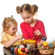 Two little girls to paint Easter eggs on a white background — Stock Photo