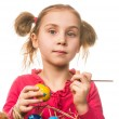 Stock Photo: Little girl drawing on the Easter eggs on a white background