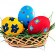 Three Easter eggs in a basket on a white background - Stock Photo