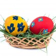 Two Easter eggs in a basket on a white background - Stock Photo