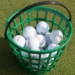 Stock Photo: Golf balls pouring out of basket onto grass