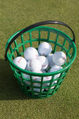 Golf balls pouring out of basket onto grass — Stock Photo