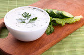 Cold soup with avocado, cucumber and yogurt on a wooden board, top view — Stock Photo