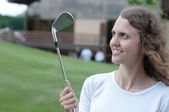 Girl golf player teeing off with driver from tee box, front view. — Stock Photo
