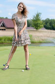 Full length view of 5 year old girl swinging golf club. — Стоковое фото