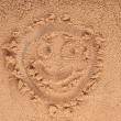 A smiley face drawing on a sand. — Stock Photo