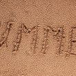 The Word Summer Written in the Sand on a Beach with Drawing of the Sun — Stock Photo #28382485