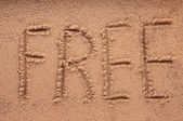 A word 'FREE' written on the sand — Stock Photo