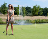 Full length view of 5 year old girl swinging golf club. — Stock Photo