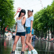 Two cheerful girls rollerblading — Stock Photo