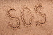SOS on the beach sand at the sea. — Stock Photo