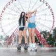 Two young sensual women skating in park — Stock Photo