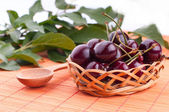 Basket of cherries on a wooden stand — Stock Photo