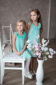 2 niñas vestidas de blanco sentado — Foto de Stock