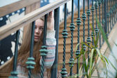 Beautiful girl sitting on wooden stairs — Stock Photo