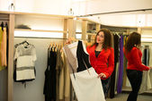 Woman shopping choosing dresses looking in mirror uncertain — Stock Photo