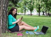 Gemischte abstammung-college-studentin, die auf dem gras liegend — Stockfoto