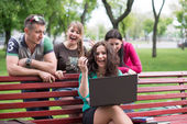 Happy group of young students sitting — Stock Photo