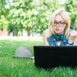 Attractive woman using laptop in the park lying — Stock Photo
