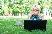 Attraktive Frau mit Laptop in den Park liegend — Stockfoto