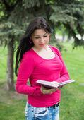 Mooi meisje leest boek in een park — Stockfoto