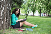 The beautiful young woman sits on a grass — Stock Photo