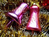Christmas and New Year decoration bells on a background of golden tinsel — Stock Photo