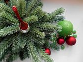 Christmas and New Year decorations red balls, firtree, green candle and stones — Stock Photo