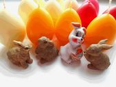 Rabbits on the background candle eggs — Stock Photo
