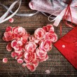 Vintage heart from flowers on wooden table — Stock Photo #13920776