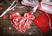 Vintage heart from flowers on wooden table — Stock Photo