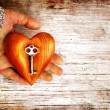 Heart with the key in women hand as a symbol of love - Stok fotoğraf
