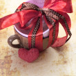 Present cup with a red ribbon bow with heart for Valentine's day — Stockfoto