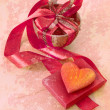 Present cup with a red ribbon bow with heart for Valentine's day — Stock Photo