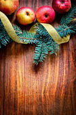 Christmas tree with apples and decorations on a wooden board — Stockfoto