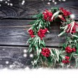 Christmas card with wreath with natural decorations hanging on a rustic wooden wall with copy space with a snow — Stock Photo #24968307