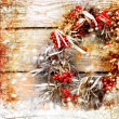 Christmas card with wreath with natural decorations hanging on a rustic wooden wall with copy space with a snow — Stock Photo #24968325
