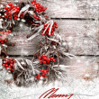 Christmas card with wreath with natural decorations hanging on a rustic wooden wall with copy space with a snow — Stock Photo #24968333
