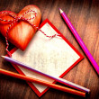 Valentines Day background with heart,pencils and framed paper for the sign on old wooden background — Stock Photo #24969189