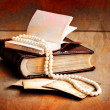 Retro picture of a necklace lying on a book - Foto Stock