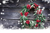 Christmas card with wreath with natural decorations hanging on a rustic wooden wall with copy space with a snow — Stock Photo