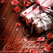 Present,gift bow with petal from flowers on wooden table, valentin day background - Stock Photo