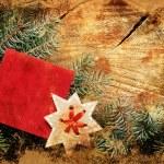Christmas decoration over grunge background, vintage paper christmas decoration with a sign and red ribbon — Stock Photo #24972215