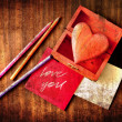 Valentines Day background with heart,pencils and framed paper for the sign on old wooden background — Stock Photo