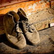 Old dirty boots.old boots worn with scratches and untied shoelaces on grunge background — Stock Photo