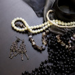 Stock Photo: Pearl necklace and earrings on black table