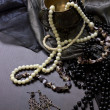 Pearl necklace and earrings on the black table - Stock Photo
