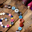 Spools of threads and buttons on old wooden table — Stock fotografie