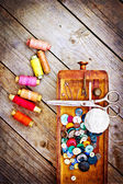 Colorful threads and old scissors on the old wooden table. — Stock Photo
